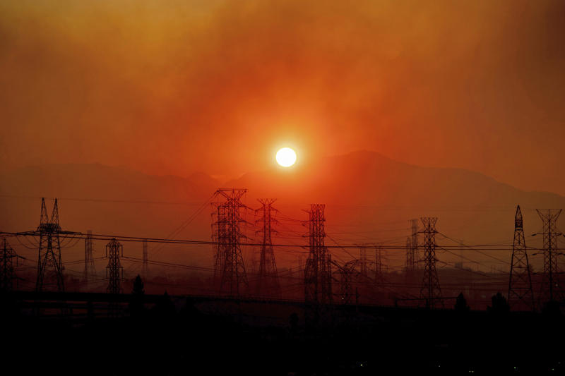 FILE - In this Friday, Oct. 11, 2019, file photo, smoke from a wildfire called the Saddle Ridge Fire hangs above power lines as the sun rises in Newhall, Calif. The destructive fire that broke out on the edge of Los Angeles began beneath a high-voltage transmission tower owned by Southern California Edison, fire officials said Monday, Oct. 14, 2019. (AP Photo/Noah Berger, File)