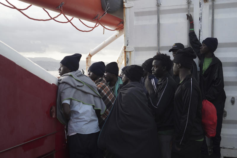 Men wait to disembark from the Ocean Viking ship as it reaches the port of Messina, Italy, Tuesday, Sept. 24, 2019.  The humanitarian ship has docked in Italy to disembark 182 men, women and children rescued in the Mediterranean Sea after fleeing Libya. (AP Photo/Renata Brito)