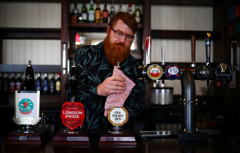 Landlord Are Kolltveit cleans the bar in the Chandos Arms pub ahead of pubs reopening following the coronavirus disease (COVID-19) outbreak, in London