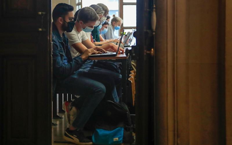 Students of the Pantheon university wearing face masks to prevent the spread of coronavirus attend a class in Paris - Michel Euler/AP