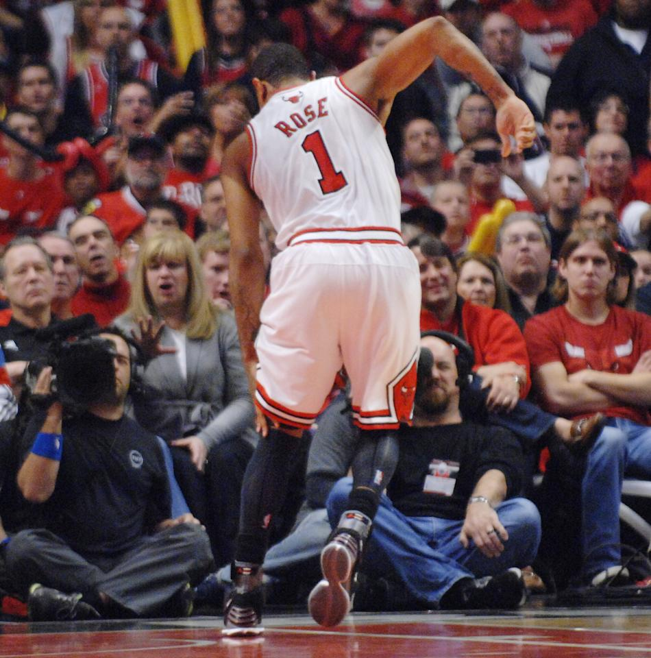 Chicago Bulls point guard Derrick Rose hobbles and holds his leg after injuring it in the fourth quarter of Game 1 in the first round of the NBA basketball playoffs against the Philadelphia 76ers Saturday, April 28, 2012, in Chicago. The Bulls won 103-91. (AP Photo/Daily Herald, John Starks) MANDATORY CREDIT; TV OUT; MAGS OUT