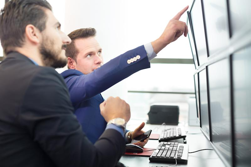 Guys in suits looking at up at a screen.
