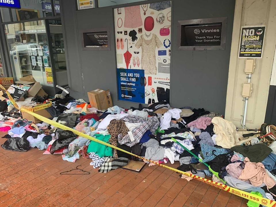 Piles of clothes and items out the front of a Vinnies store