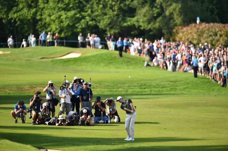Rory McIlroy chips onto the 18th on his way to a share of the lead at the  PGA Championship at Wentworth