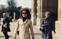 <p>A double-breasted wool camel coat and a black turtleneck—and her signature hairstyle—are Jackie's clothing of choice for a visit to Paris in the late '60s.<br></p>