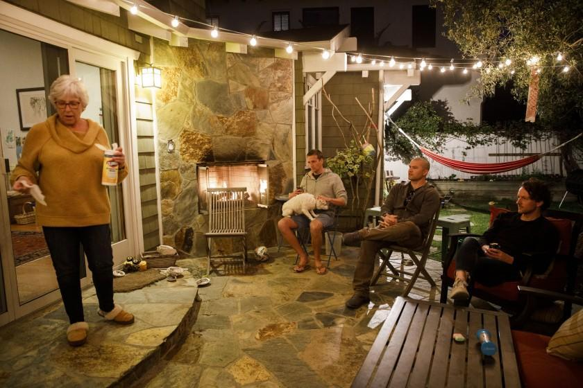 """Deborah Herzik pulls out Clorox wipes to clean chairs and a cooler as her son and his friends share dinner """"together"""" while social distancing in the family's backyard. <span class=""""copyright"""">(Patrick T. Fallon / Los Angeles Times)</span>"""
