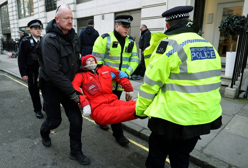 Greenpeace climate activist looks on as she is being removed by police officers near the entrance to BP's head office in London