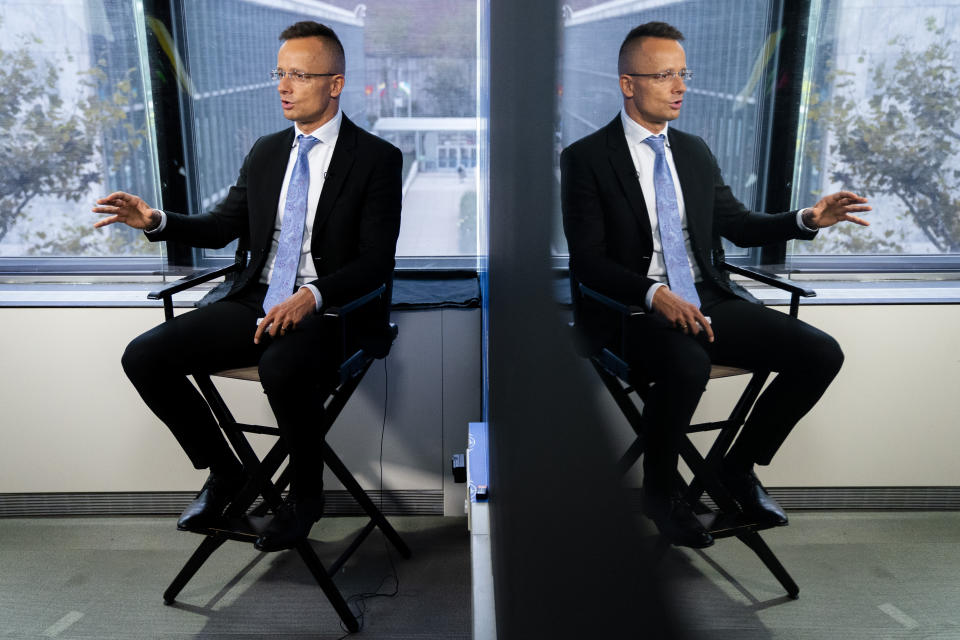 Peter Szijjarto, Hungary's minister of foreign affairs and trade, is reflected in studio glass as he speaks during an interview with the Associated Press at United Nations headquarters, Thursday, Sept. 23, 2021, during the 76th Session of the U.N. General Assembly in New York. (AP Photo/John Minchillo)