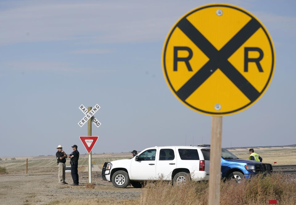 Law enforcement officials stand at a railroad crossing, Sunday, Sept. 26, 2021, just west of where an Amtrak train derailed the day before near Joplin, Mont., killing three people and injuring others. The westbound Empire Builder was en route to Seattle from Chicago, with two locomotives and 10 cars. (AP Photo/Ted S. Warren)