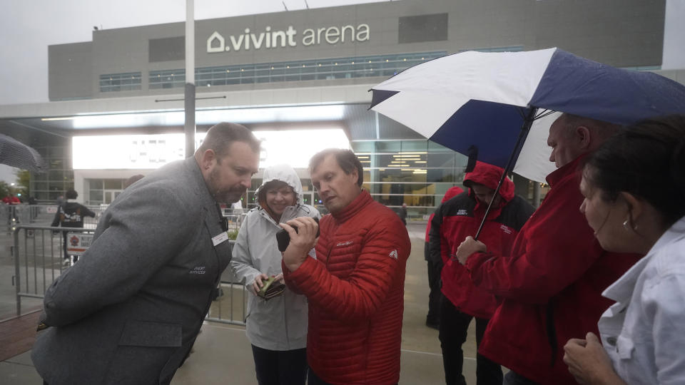 Utah Jazz security, left, looks for proof of vaccination or a negative test from fans before attending a preseason NBA basketball game Monday, Oct. 11, 2021, in Salt Lake City. In Utah, the NBA's Jazz is making its employees get vaccinated. It is also requiring fans at games to show proof of vaccination or a negative COVID test. So far, just a few ticket refunds have been needed, and the season opener is expected to be sold out by next week, said Jazz spokesman Frank Zang. (AP Photo/Rick Bowmer)