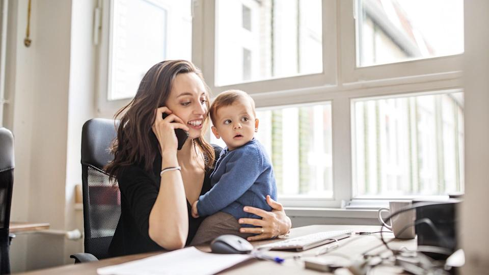 Young woman sitting at table with her son talking on mobile phone in office.