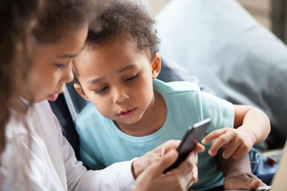 children using smartphone together at home