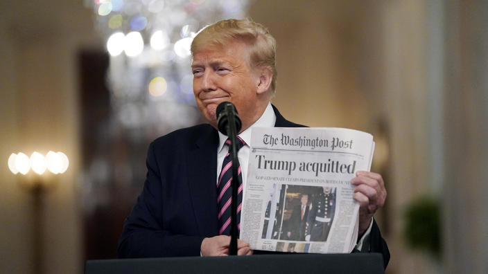 President Trump holds a copy of the Washington Post in the East Room on Feb. 6. (Evan Vucci/AP)