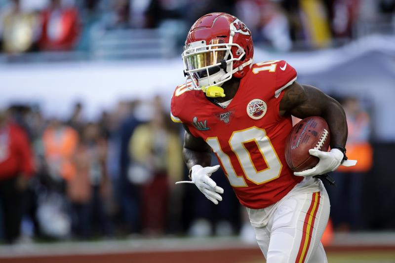 Tyreek Hill runs with the ball in his arm during a game.