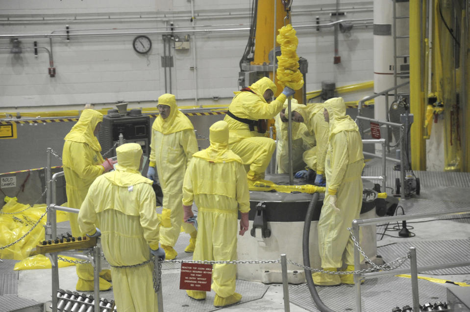 In this May 7, 2013 photo released by Idaho National Laboratory shows Nuclear operations professional personnel work above the Advanced Test Reactor at Idaho National Laboratory's desert site about 50 miles west of Idaho Falls, Idaho. The small cylindrical section in the center of the platform has access ports that allow access to the reactor core for refueling and experiment loading and unloading during routine outages. The platform, a layer of shield blocks totalling more than 150,000 lbs, and then the 62,000-lb reactor vessel top head are temporarily removed in order to complete the ATR core overhaul. (Idaho National Laboratory via AP)