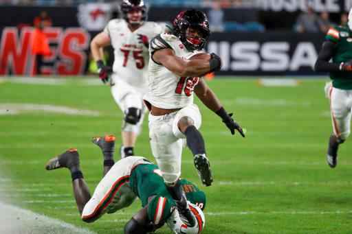 Louisville running back Javian Hawkins (10) runs out of bounds as he avoids a tackle by Miami safety Amari Carter (5) during the second half of an NCAA college football game Saturday, Nov. 9, 2019, in Miami Gardens, Fla. Miami won 52-27. (AP Photo/Wilfredo Lee)
