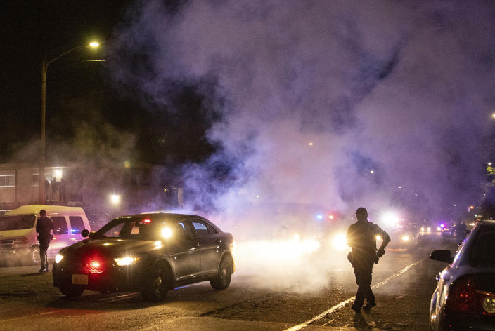 Oakland police officers walk through smoke as several hundred demonstrators confront them during a protest against police brutality in Oakland, Calif., on Friday, April 16, 2021. (AP Photo/Ethan Swope)