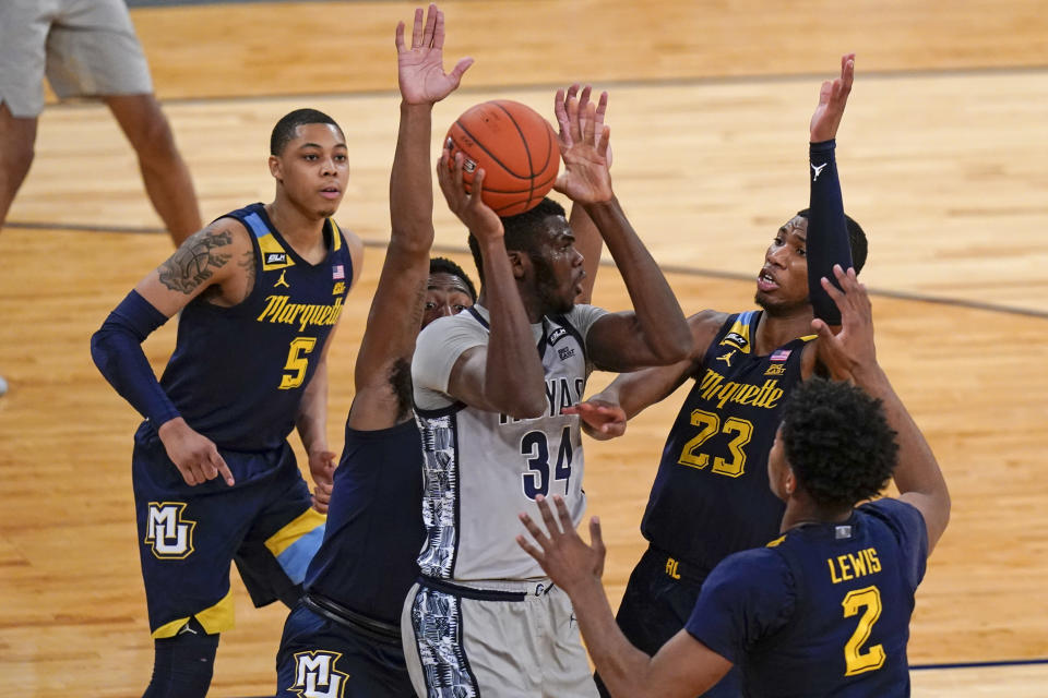 Georgetown's Qudus Wahab (34) passes away from Marquette's Greg Elliott (5), Jamal Cain (23), Justin Lewis (2) and Symir Torrence during the second half of an NCAA college basketball game in the Big East conference tournament Wednesday, March 10, 2021, in New York. (AP Photo/Frank Franklin II)