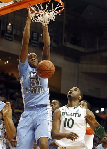 North Carolina's John Henson (31) dunks over Miami's Raphael Akpejiori (10) during the first half of an NCAA college basketball game, Wednesday, Feb. 15, 2012, in Coral Gables, Fla. (AP Photo/Lynne Sladky)