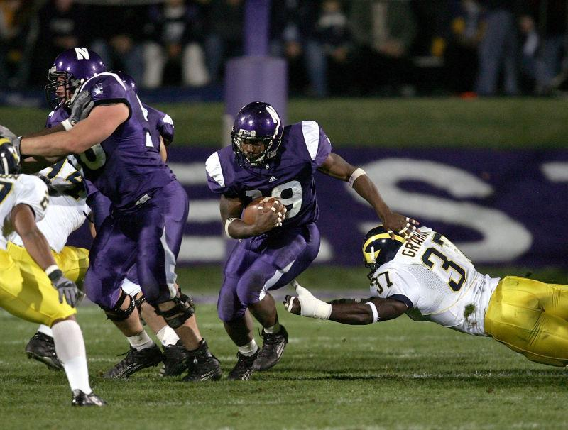 Running back Tyrell Sutton #19 of the Northwestern Wildcats follows the block of lineman Ryan Keenan #56 as linebacker Chris Graham #37 of the Michigan Wolverines dives for a tackle during a game on October 29, 2005 at Ryan Field at Northwestern University in Evanston, Illinois.