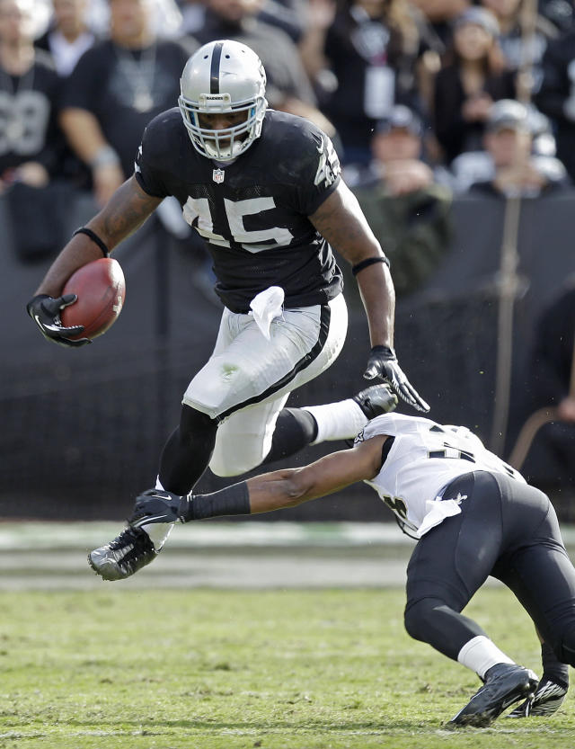 Oakland Raiders fullback Marcel Reece, top, carries the ball over New Orleans Saints cornerback Jabari Greer during the first quarter of an NFL football game in Oakland, Calif., Sunday, Nov. 18, 2012. (AP Photo/Ben Margot)