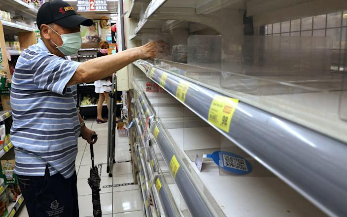 A man reaches for instant noodles from a near-empty shelf as customers rush to buy groceries in Taipei - ANN WANG/REUTERS