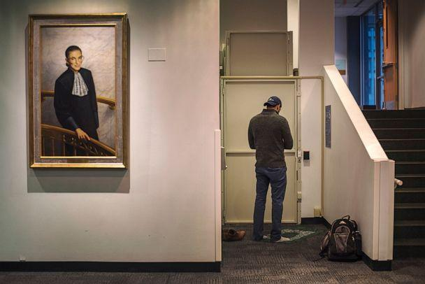 PHOTO: A man prays next to a portrait of Supreme Court justice Ruth Bader Ginsburg at the Columbia University Law School. (Sana Ullah)