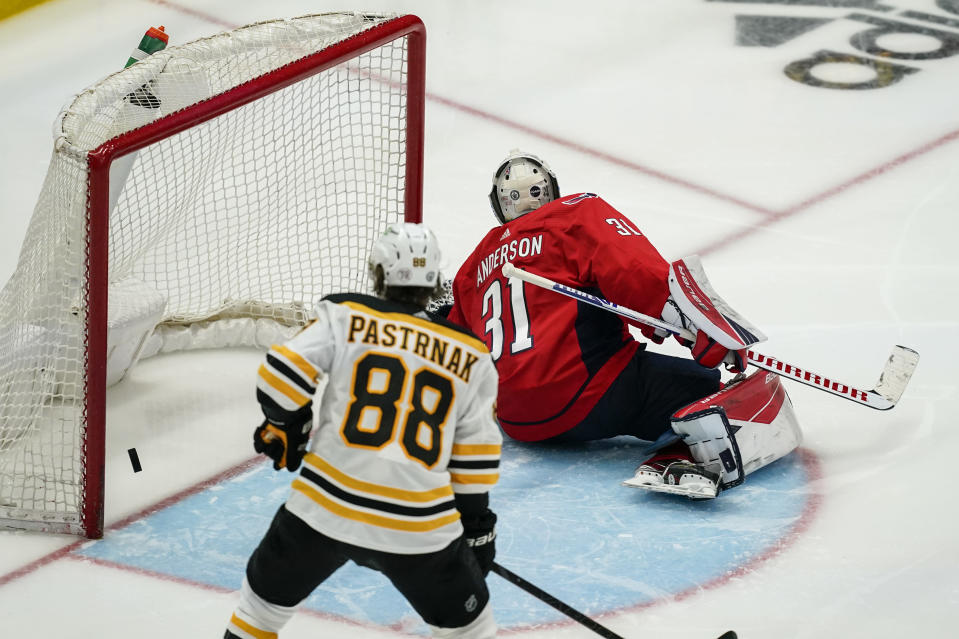 Washington Capitals goaltender Craig Anderson (31) cannot stop the winning goal by Boston Bruins center Brad Marchand (not shown) with Bruins right wing David Pastrnak (88) nearby during overtime of Game 2 of an NHL hockey Stanley Cup first-round playoff series Monday, May 17, 2021, in Washington. (AP Photo/Alex Brandon)