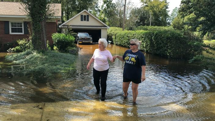 Vivian Chestnut, left, and her neighbor Morgan Sellers walk through floodwaters around Chestnut's home in Conway, S.C., on Monday, Sept. 17, 2018. Chestnut and Sellers worry the decision by the state of South Carolina to build a higher wall on the main highway to Myrtle Beach to keep it open might push more floodwaters from the Waccamaw River into neighborhoods. The state says the effect will be negligible. (AP Photo/Jeffrey Collins)