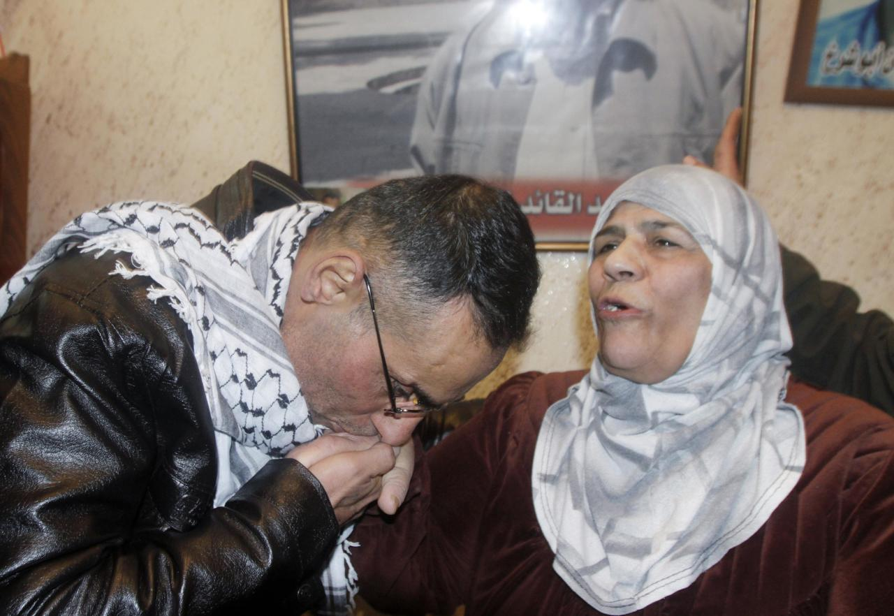 Newly released Palestinian prisoner Ibraheem Taktook (L) kisses his aunt's hand upon his arrival at his home in the West Bank city of Nablus early December 31, 2013. Israel freed 26 Palestinian prisoners, including Taktook, on Tuesday, days before U.S. Secretary of State John Kerry was due back in the Middle East to press the two sides to agree a framework peace deal. REUTERS/Abed Omar Qusini (WEST BANK - Tags: POLITICS CIVIL UNREST)