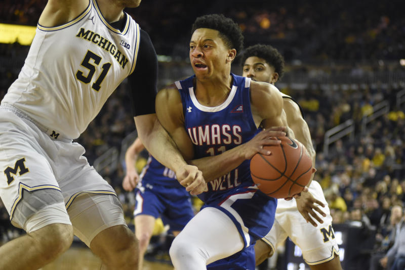 UMass-Lowell guard Obadiah Noel, right, goes to the basket as he is guarded by Michigan forward Austin Davis during the first half of an NCAA college basketball game, Sunday, Dec. 29, 2019, in Ann Arbor, Mich. (AP Photo/Jose Juarez)