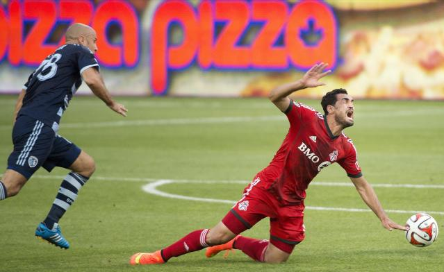 Toronto FC forward Gilberto, right, gets tripped up by Sporting Kansas City midfielder Victor Munoz during the first half of an MLS soccer game Saturday, July 26, 2014, in Toronto. (AP Photo/The Canadian Press, Nathan Denette)