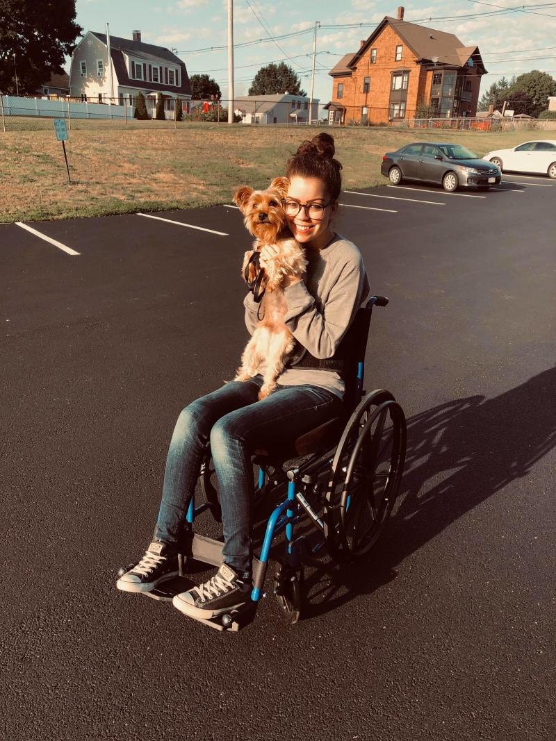 Jennifer in her wheelchair holding her small dog.