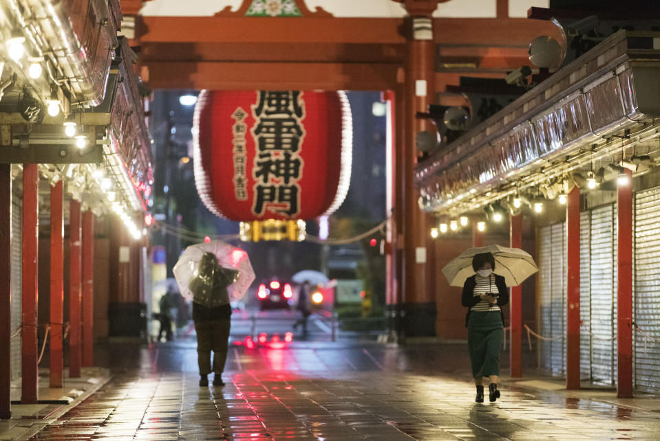 People walk in the rain past souvenir shops lining a passageway to Sensoji temple in Tokyo on Friday, Oct. 9, 2020. A slow-moving typhoon off Japan's southern coast has triggered gusts and rain across a large part of the country and could bring heavy rains to the Tokyo region through early next week, though it was not expected to make landfall, officials said Friday. (AP Photo/Hiro Komae)