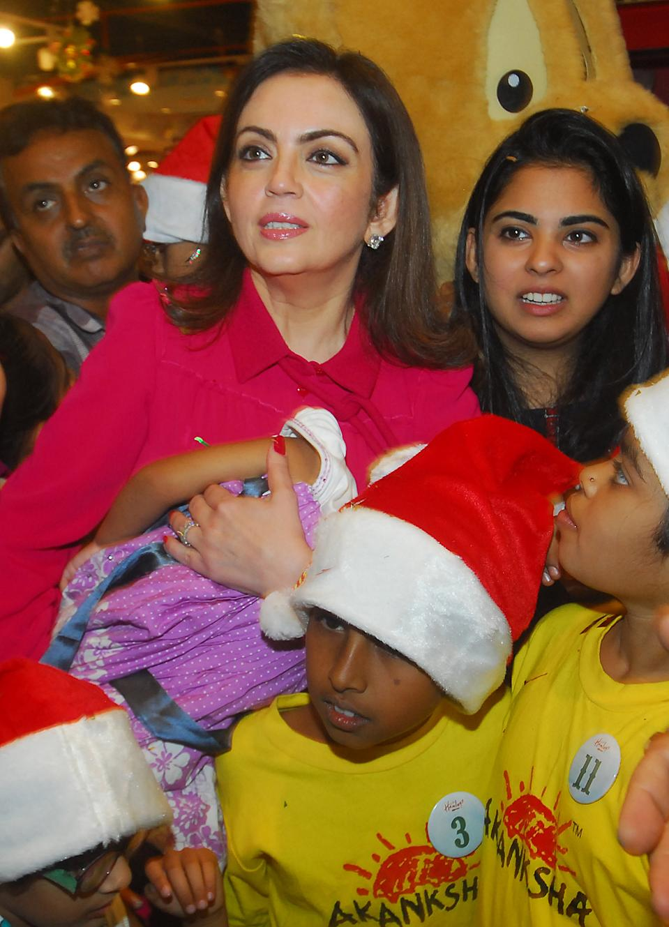 MUMBAI, INDIA - DECEMBER 24: Nita Ambani, Chairperson of Reliance Foundation with her daughter Isha and the special Kids of Drishti & Akansha during the Christmas celebration at Hamleys Store on December 24, 2012 in Mumbai, India. (Photo by Prodip Guha/Hindustan Times via Getty Images)