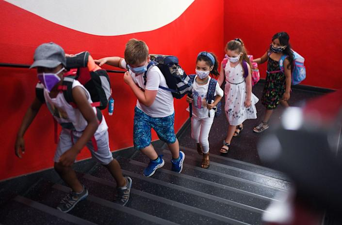 Young kids in masks walk up the stairs against a red wall at a primary school.