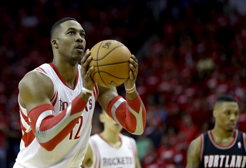 Houston Rockets' Dwight Howard (12) shoots a free throw against the Portland Trail Blazers during overtime in Game 1 of an opening-round NBA basketball playoff series Sunday, April 20, 2014, in Houston. The Trail Blazers won 122-120 in overtime. Howard was 9-for-17 in free throws. (AP Photo/David J. Phillip)