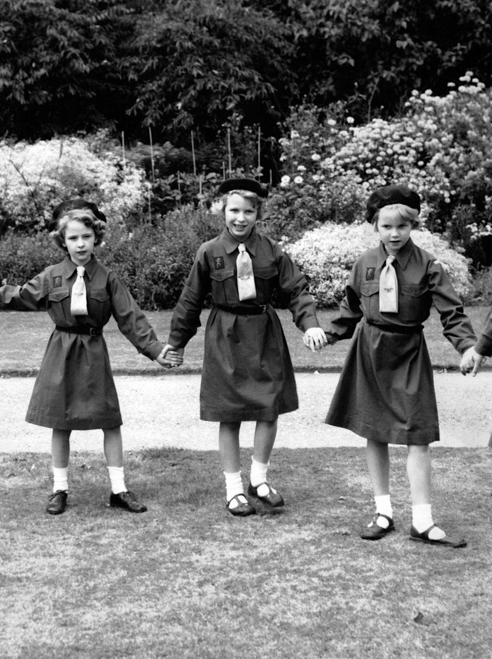 <p>Princess Anne and two fellow Brownies pose for a photo in their uniforms on the grounds of Buckingham Palace.</p>