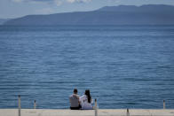 A couple sits at the seafront in Opatija, Croatia, Saturday, May 15, 2021. Croatia has opened its stunning Adriatic coastline for foreign tourists after a year of depressing coronavirus lockdowns and restrictions. (AP Photo/Darko Bandic)