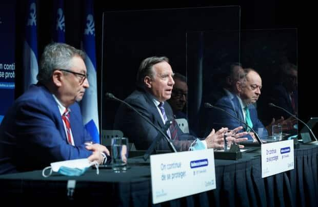 Quebec Premier Francois Legault delivers remarks next to Health Minister Christian Dube and Quebec Director of Public Health Dr. Horacio Arruda. (Paul Chiasson/The Canadian Press - image credit)