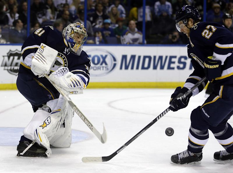 St. Louis Blues goalie Jaroslav Halak, left, of Slovakia, clears a puck past teammate Alex Pietrangelo, right, during the first period of an NHL hockey game against the Pittsburgh Penguins, Saturday, Nov. 9, 2013, in St. Louis. (AP Photo/Jeff Roberson)