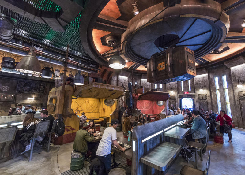 "Docking Bay 7 Food and Cargo is a designated location for traveling food shuttles (the Galaxy&#39;s Edge equivalent of food trucks). It&#39;s where the alien chef Strono &quot;Cookie"" Tuggs, formerly the cook in Maz Kanata&#39;s castle, serves meals to hungry guests. Tuggs&#39;s mobile kitchen and restaurant is made from a modified <a href=""https://starwars.fandom.com/wiki/Sienar-Chall_Utilipede-Transport"">Sienar-Chall Utilipede-Transport</a>, a starship designed specifically for the Disney park. (Photo: Joshua Sudock/Disney Parks)"
