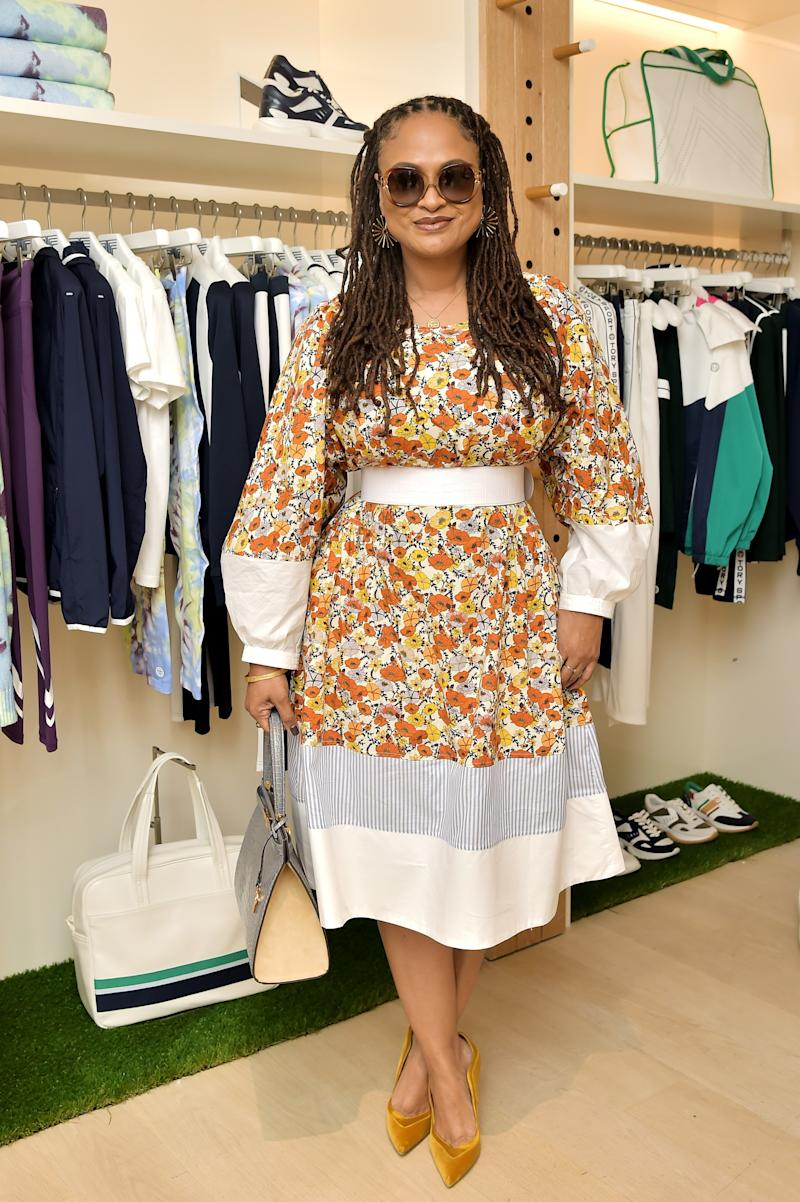 Ava DuVernay is wearing the Printed Cotton Dress, Lee Radziwill Bag, Horseshoe Nail Hoop Earring, and Robinson Butterfly Sunglasses.