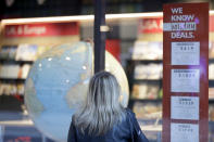 A woman looks at ads in the window of a closed travel agent office in Sydney, on Aug. 13, 2021. Japan, Australia and New Zealand all got through the first year of the coronavirus pandemic in relatively good shape, but now are taking very divergent paths in dealing with new outbreaks of the fast-spreading delta variant. (AP Photo/Rick Rycroft)