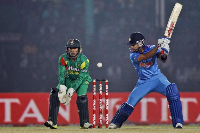 India's Virat Kohli, right, plays a shot as Bangladesh's wicketkeeper Anamul Haque watches during the Asia Cup one-day international cricket tournament between them in Fatullah, near Dhaka, Bangladesh, Wednesday, Feb. 26, 2014. (AP Photo/A.M. Ahad)