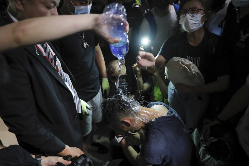 A protester pours water on a detained man, who protesters claimed was a police officer from mainland China, during a demonstration at the Airport in Hong Kong, Tuesday, Aug. 13, 2019. (Photo: Kin Cheung/AP)