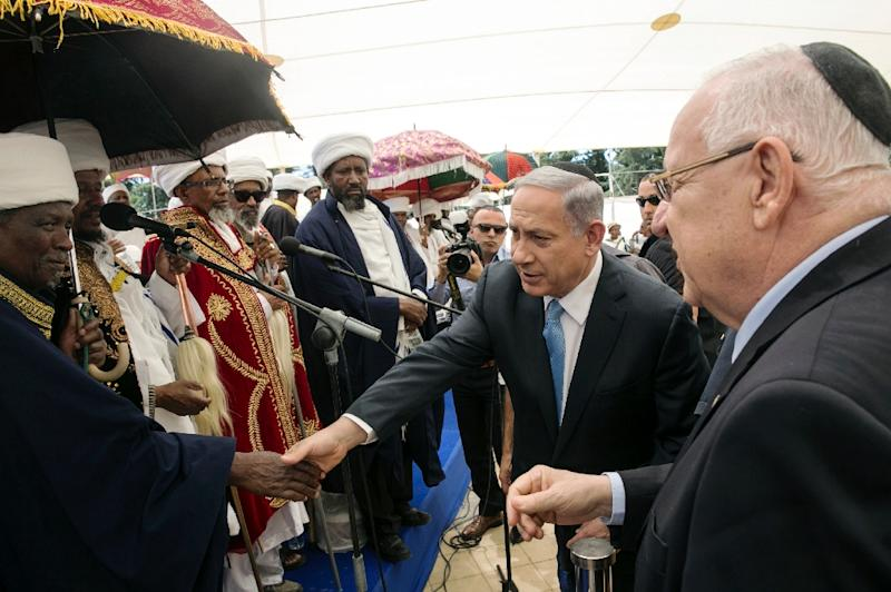 Israeli Prime Minister Benjamin Netanyahu (C) and President Reuven Rivlin (R) shake hands with Israelis of Ethiopian descent during a ceremony on Mount Herzl in Jerusalem on May 17, 2015