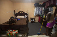 Deportees Jhon Celestin lies on a bed as he talks on the phone, while his wife Delta De Leon sweeps the floor of their temporary bedroom, in a relative's home in Port-au-Prince, Haiti, Thursday, Sept. 23, 2021. The couple are among the more than 1,900 migrants that the U.S. expelled to Haiti this week. (AP Photo/Joseph Odelyn)