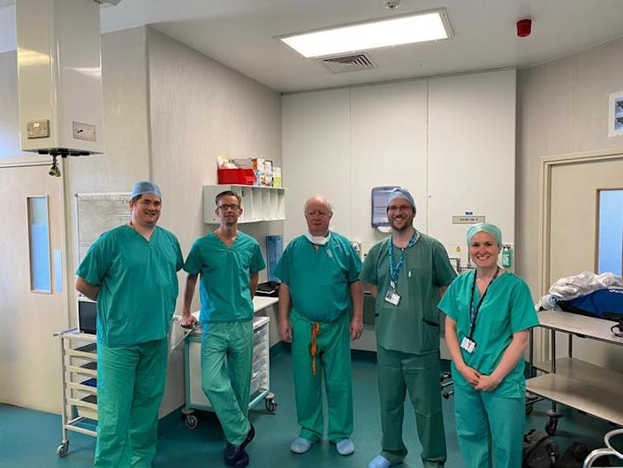 Five people stand in an operating theatre wearing medical scrubs.