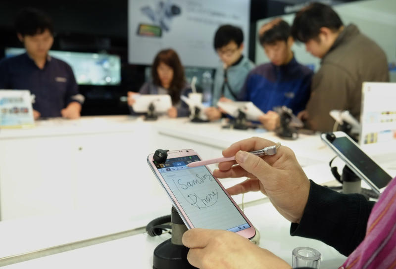 In this April 10, 2013 photo, a customer doodles on a new Samsung smartphone at a retail shop in Taipei, Taiwan. Taiwanese companies have long viewed tech giant Samsung as a major threat and the battle has recently appeared to tilt in favor of the South Korean rival as Taiwan's smartphone, memory chip and display panel makers suffered sagging exports. The sales erosion has been driven by competition, some of it from South Korea, and a weak global economy but has also spawned fears on this export-reliant island of 23 million that Samsung has deliberately targeted Taiwanese firms as part of a campaign to undermine their competitiveness in markets around the world. (AP Photo/Wally Santana)